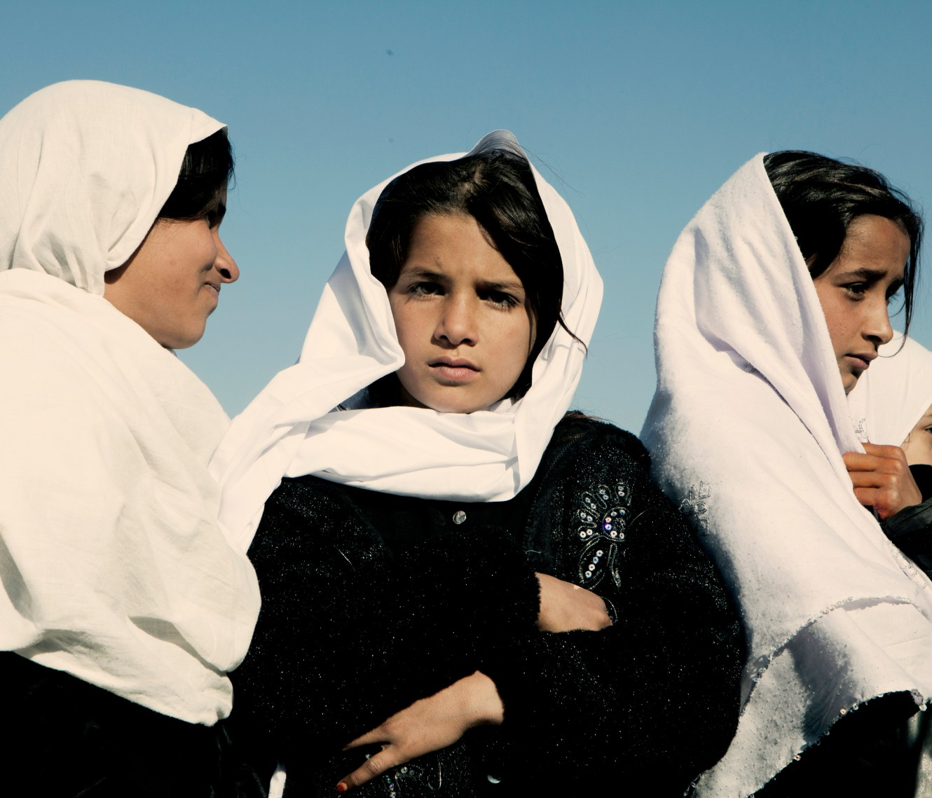 Three school girls wearing white veils. In June 2011, President Obama announced his plan to begin the withdrawal of US troops from Afghanistan, but there is currently no end date for the war in the troubled country. Helmand is the largest province in Afghanistan, and the heart of the war against terror. Commanders on the ground have described the situation as the most brutal conflict the British Army has been involved in since the Korean War. Much of the fighting between NATO and Taliban forces is taking place in this province and Helmand is a true Taliban stronghold. The Helmand River flows through the mainly desert region. With these images I am trying to show a softer side to this troubled area of Afghanistan.