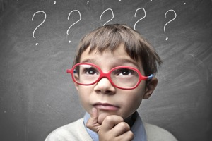 child with glasses and questioning look in front of a chalkboard full of question marks