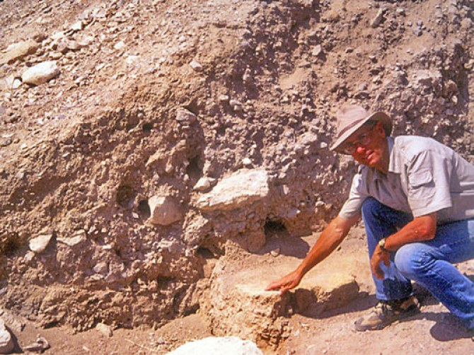 Wood points to collapsed mud bricks from the city wall that fell to the base of the retaining wall at Jericho