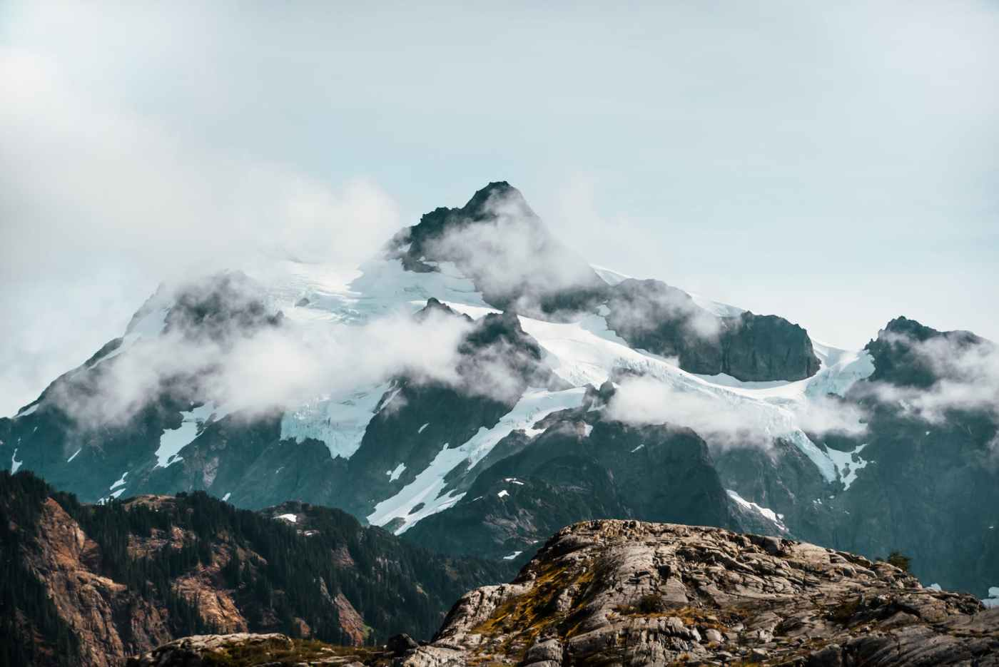 snowy mountain ridge against in clouds