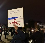 A protester proudly displays his sign, a hand-drawn representation of the contrast between oil and water.