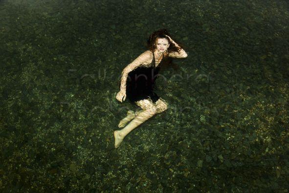 Deutschland, Bayrischer Wald, junge Frau im Sommekleid unter Wasser