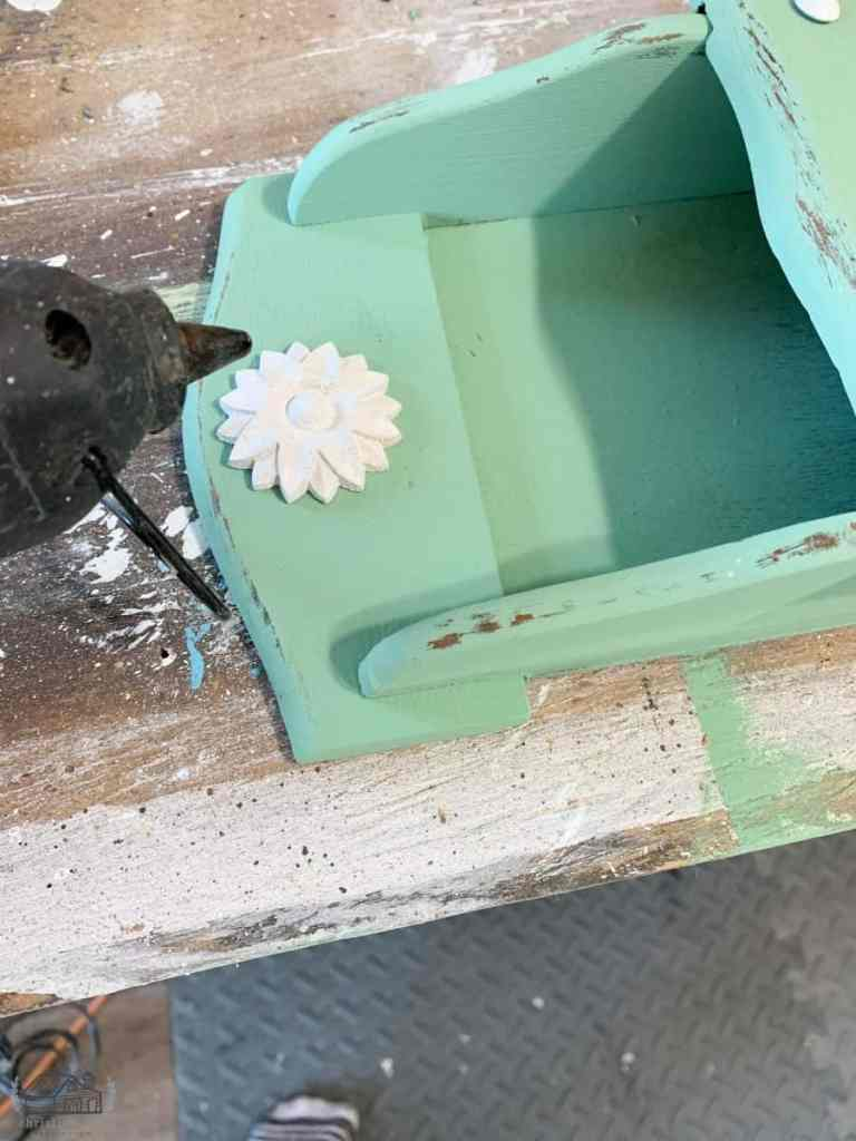 Using Hot Glue to Attach Wood Floral Appliques to Mail Sorter.