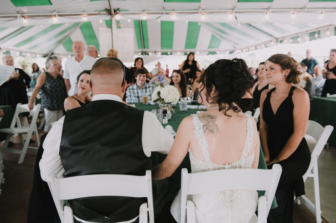 Bride and groom sitting enjoying their guests at a Fishkill Golf Course wedding