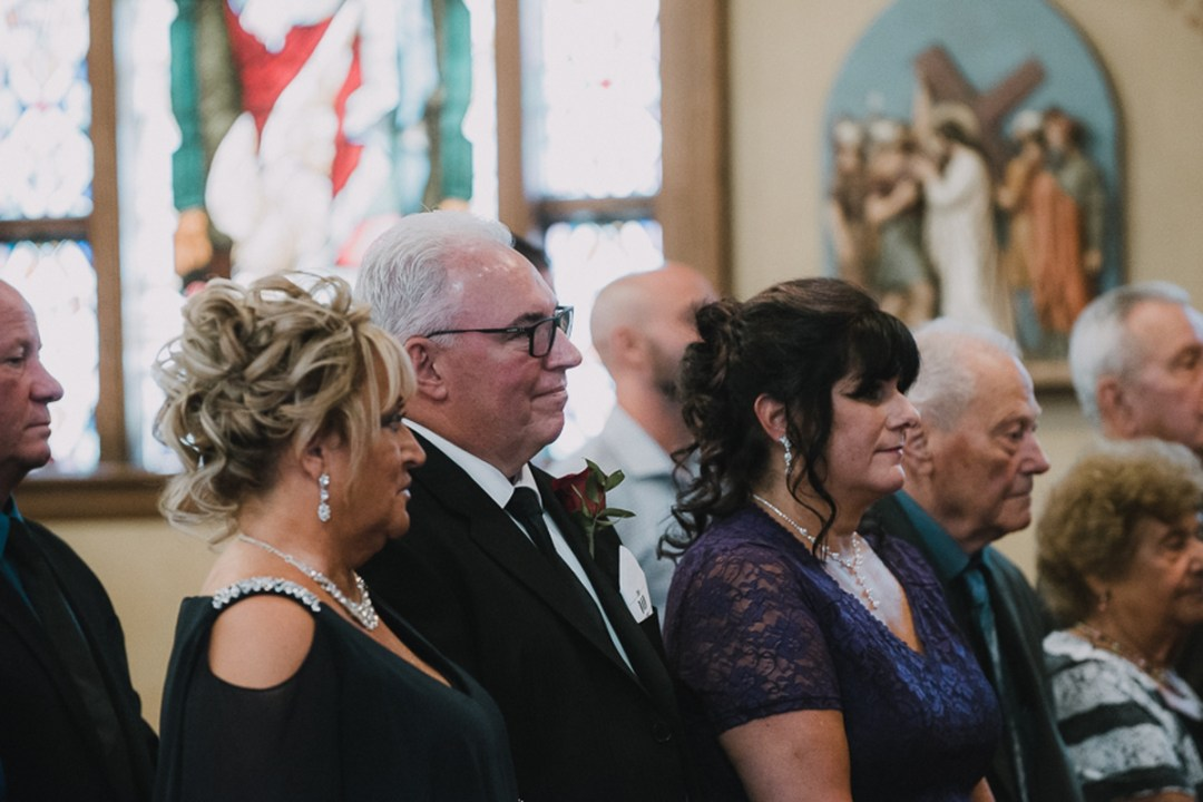 Wedding guests enjoying ceremony at Our Lady Of Loretto church in Cold Spring, NY