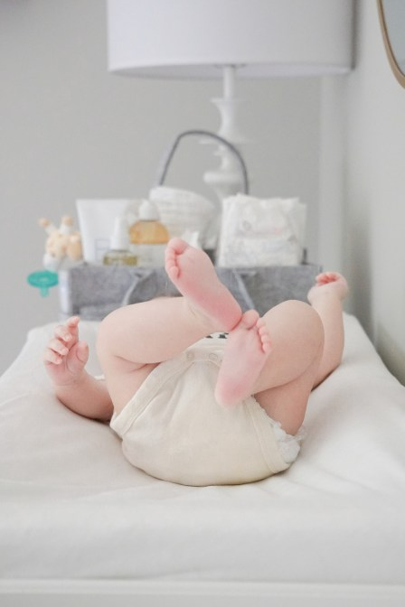 Close up of baby feet while baby is laying on changing pad, diaper caddy in the background/Newborn Essentials