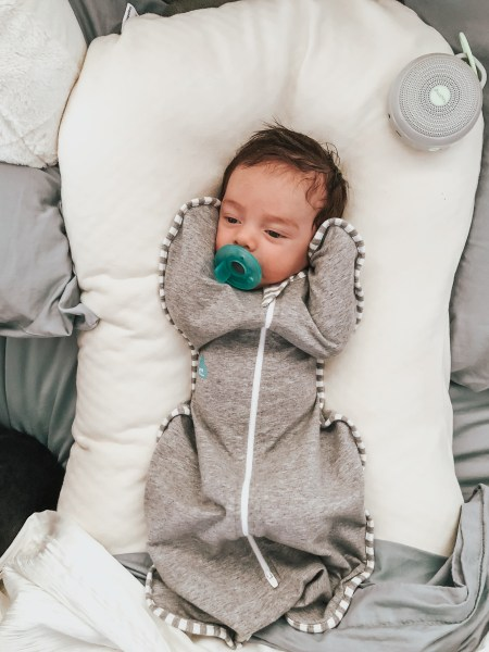 Infant laying in a SnuggleMe, wearing a LoveToDream swaddle, pacifier in mouth/newborn essentials