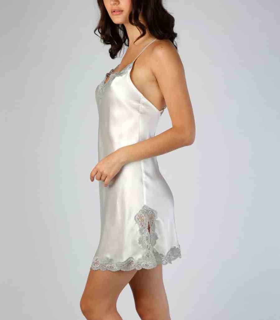 silk white chemise with lace is worn by a women posed to the side