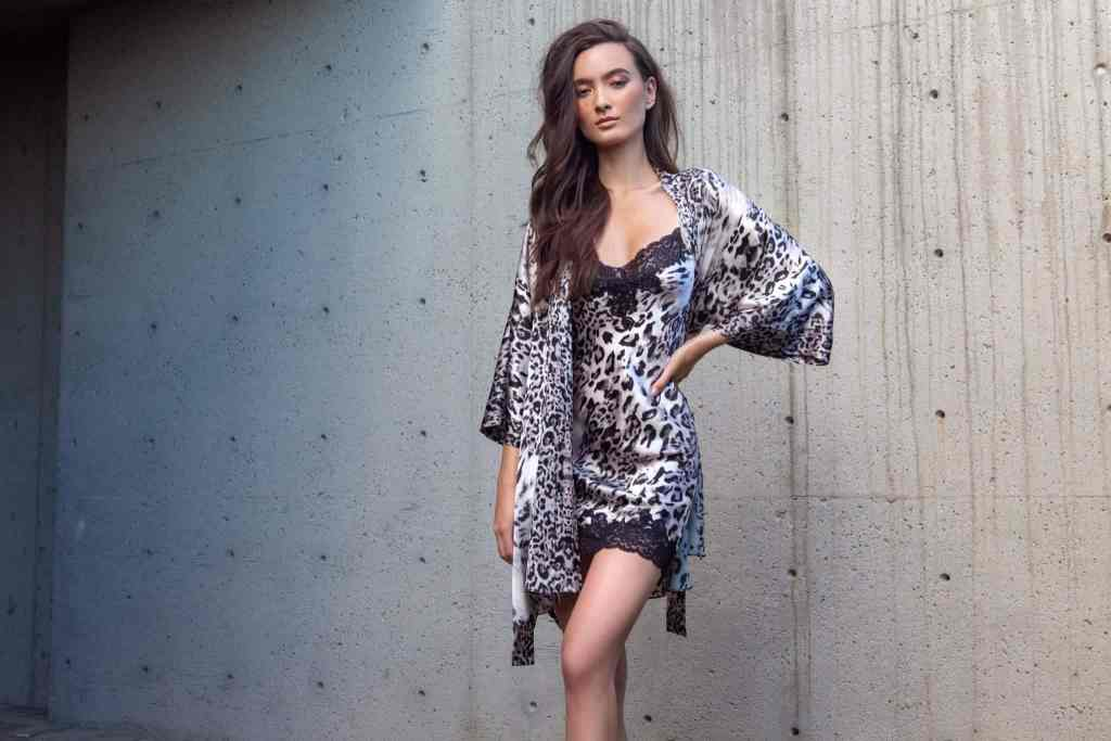 A silk chemise with our Christine Lingerie Femme Fatal leopard print with black lace is paired with a silk short robe with the leopard print is worn by women standing in front of a concrete wall