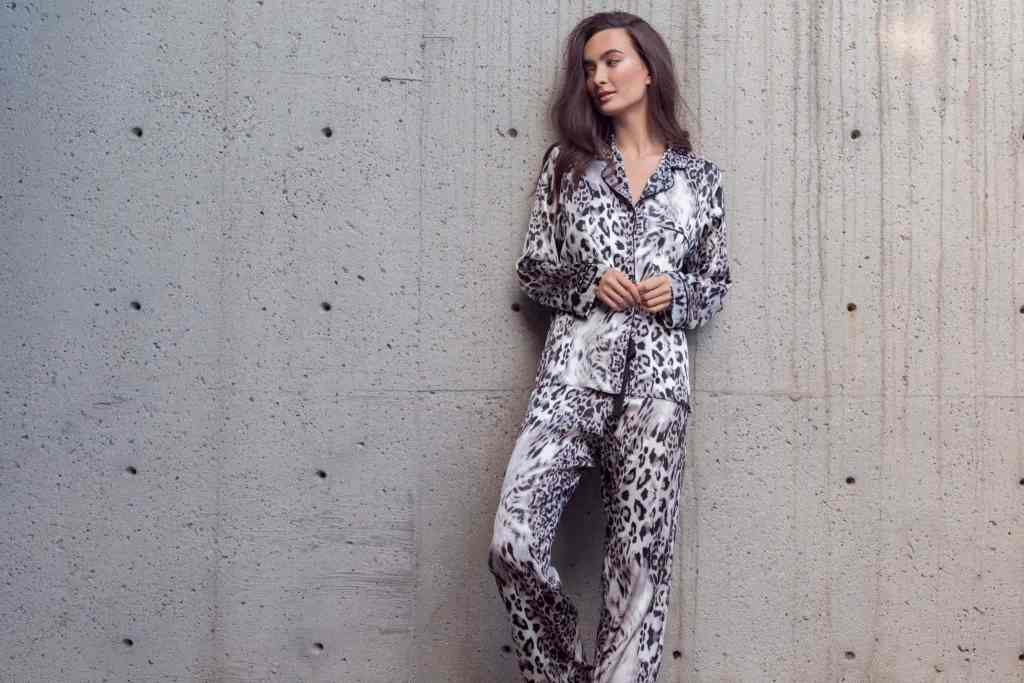 A silk pajama set with our Christine Lingerie Femme Fatal leopard print is worn by a women leaning on a concrete wall