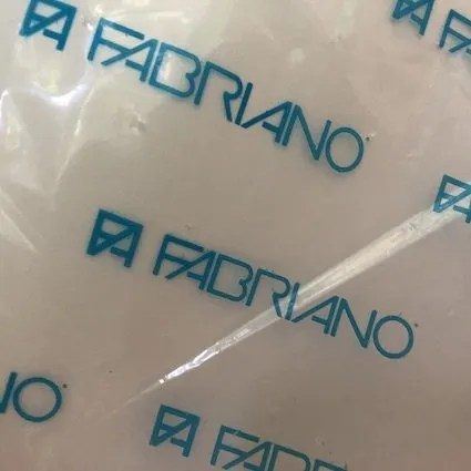 Photo of the plastic covering of a packet of Fabriano watercolour paper. The section photographed shows the blue Fabriano name and the factory's symbol.