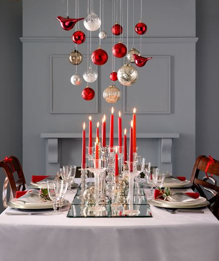 Pair rich shades of red with pops of metallics and focus on layers like creating a DIY runner out of mirrors. Varying scale (candlesticks on tabletop and ornaments hung from a chandelier) will also help to create strong visual interest