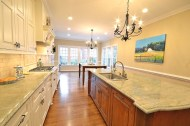 Raised panel cabinetry, Coast Green granite, integrated Miele dishwasher, oiled bronze fixtures