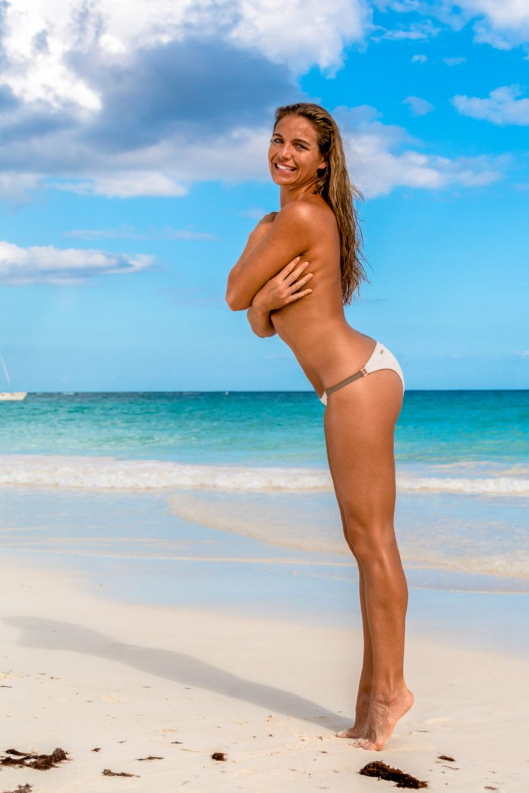 Corky, topless but covering herself with her hands, up on tiptoe in a white and brown bikini bottom on the beach in Tulum, Mexico. Photo by Christopher Keelty.