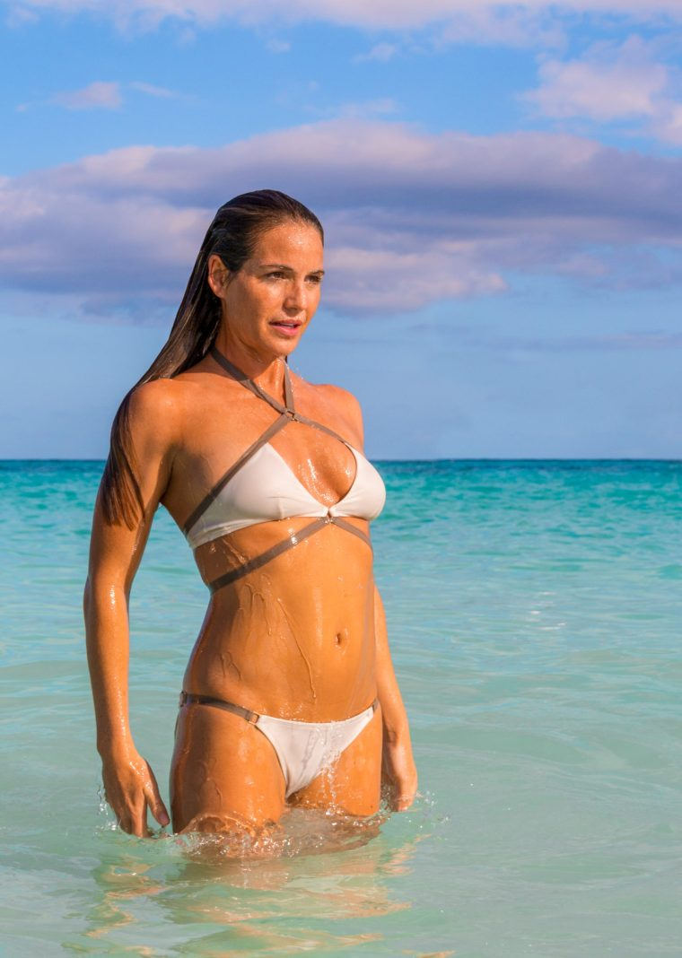 Corky, in a white and brown bikini, rises out of the ocean in Tulum, Mexico. Photo by Christopher Keelty.
