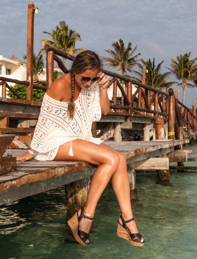 Corky seated on a wooden bridge with legs hanging toward the water, near the beach in Isla Mujeres, Mexico. Photo by Christopher Keelty