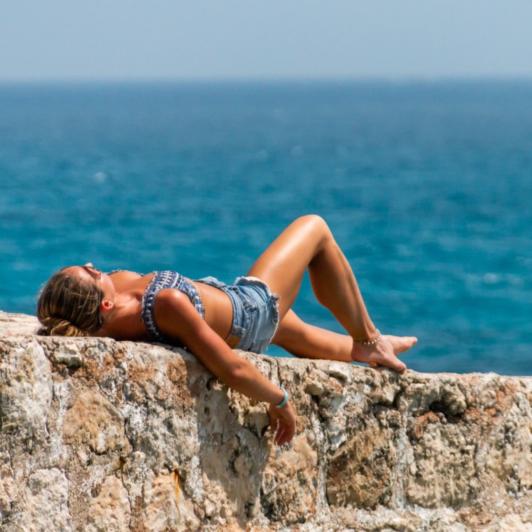 Model Corky lays back on a wall, wearing daisy dukes a knit top, in Isla Mujeres, Mexico. Photo by Christopher Keelty.