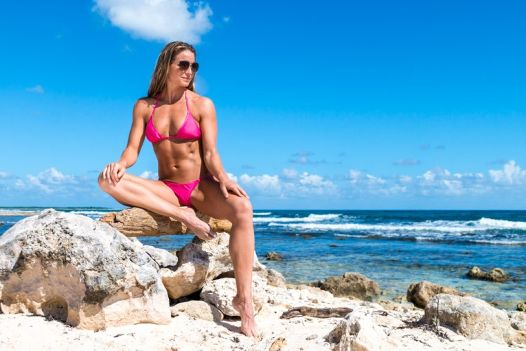 Corky seated on a log in a bikini on the beach in Cozumel, Mexico. Photo by Christopher Keelty