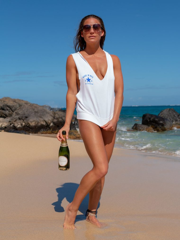 Model Corky holds a bottle of champagne at the beach in Saint Martin