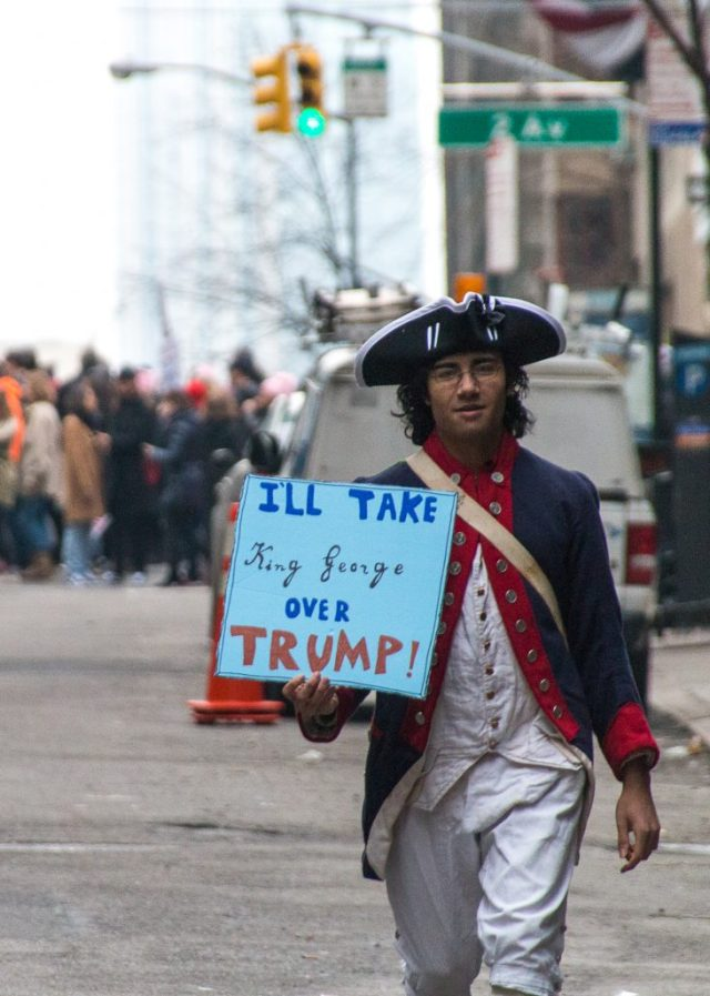 """A young man at the New York City Women's March, dressed in costume as a minuteman and holding a sign that reads """"I'll take King George over Trump."""""""