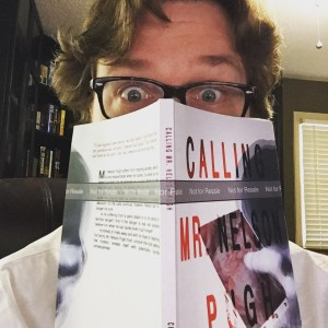 Image of Christopher Opyr with wavy brown hair, peeking over the top of a print proof of Calling Mr. Nelson Pugh.