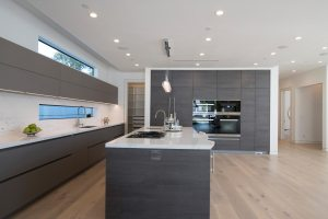Modern German kitchen cabinetry with no handles from Bauformat USA, white countertops and undermount kitchen sinks.