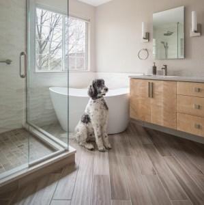 Transitional bathroom with floating figured maple vanity and freestanding Neptune Rouge acrylic bathtub.