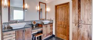 Custom walnut bathroom cabinetry with makeup vanity and linen cabinet, with Aquabrass vessel faucets.