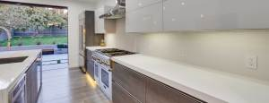 Bauformat modern grey German kitchen cabinetry with white countertops.