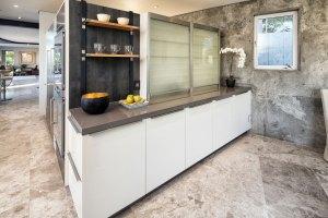 Modern matte white kitchen cabinets in wet bar with glass servodrive doors.