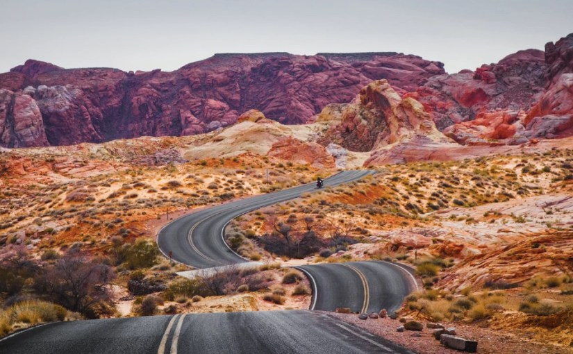 A windy road is seen up and down in red rock desert