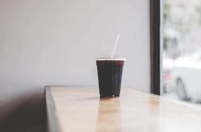 plastic to-go cup filled with iced coffee on a wooden bench