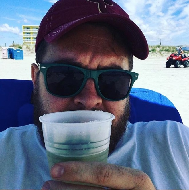 Selfie of me with a margarita in a clear plastic cup on a beach