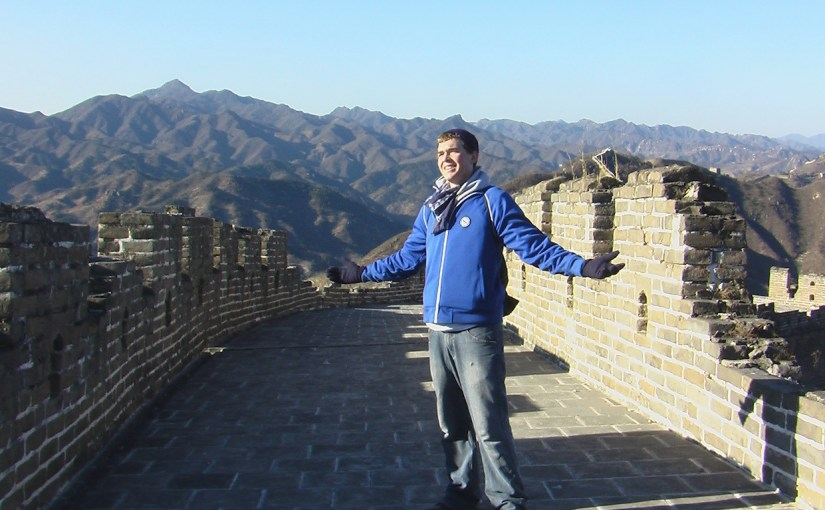 Christopher Wink in blue jacket with arms spread wide on the Great Wall of China