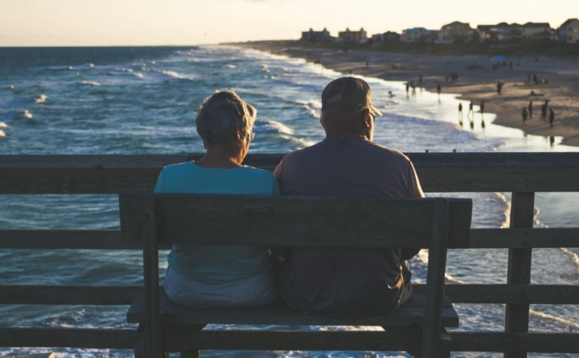 an elderly couple on a bench looking at the ocean