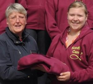 Der Förderkeis-Mitglied Ilse Pohl-Ringkamp übergibt Teamer-Jacken für das Konfi-Camp
