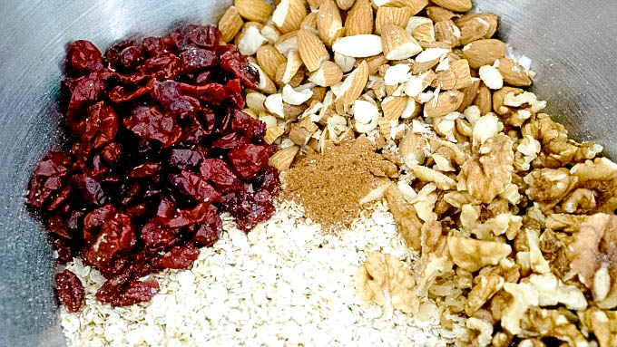 Ingredients separated within mixing bowl for pear and cranberry granola