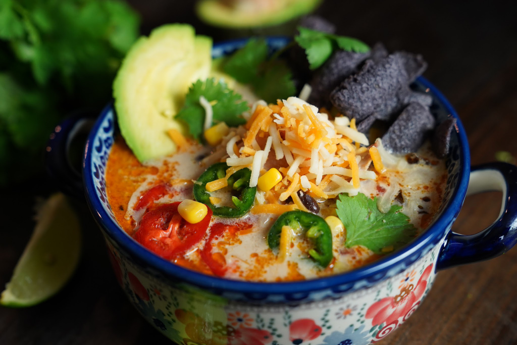 bowl of creamy chicken tortilla soup with cilantro, jalapeño, and lime