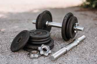 dumbbell near plates and metal collars on asphalt