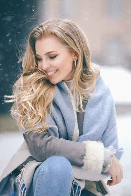 smiling young woman enjoying snow day in park