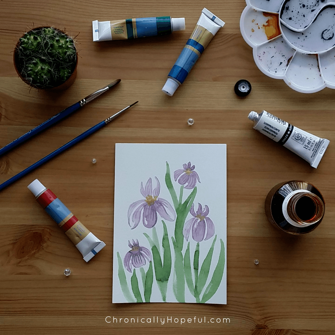 Watercolour Irises on a card, paints and brushes scattered on table around it