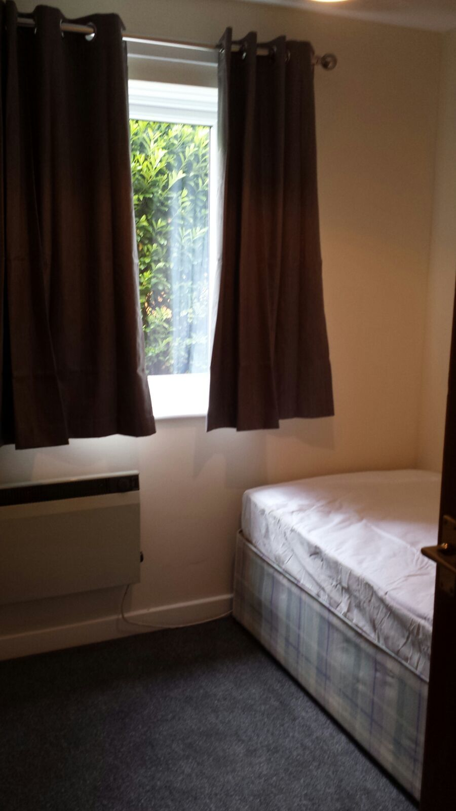 a small box room with a single bed which covers half the room, spanning from wall to wall.
