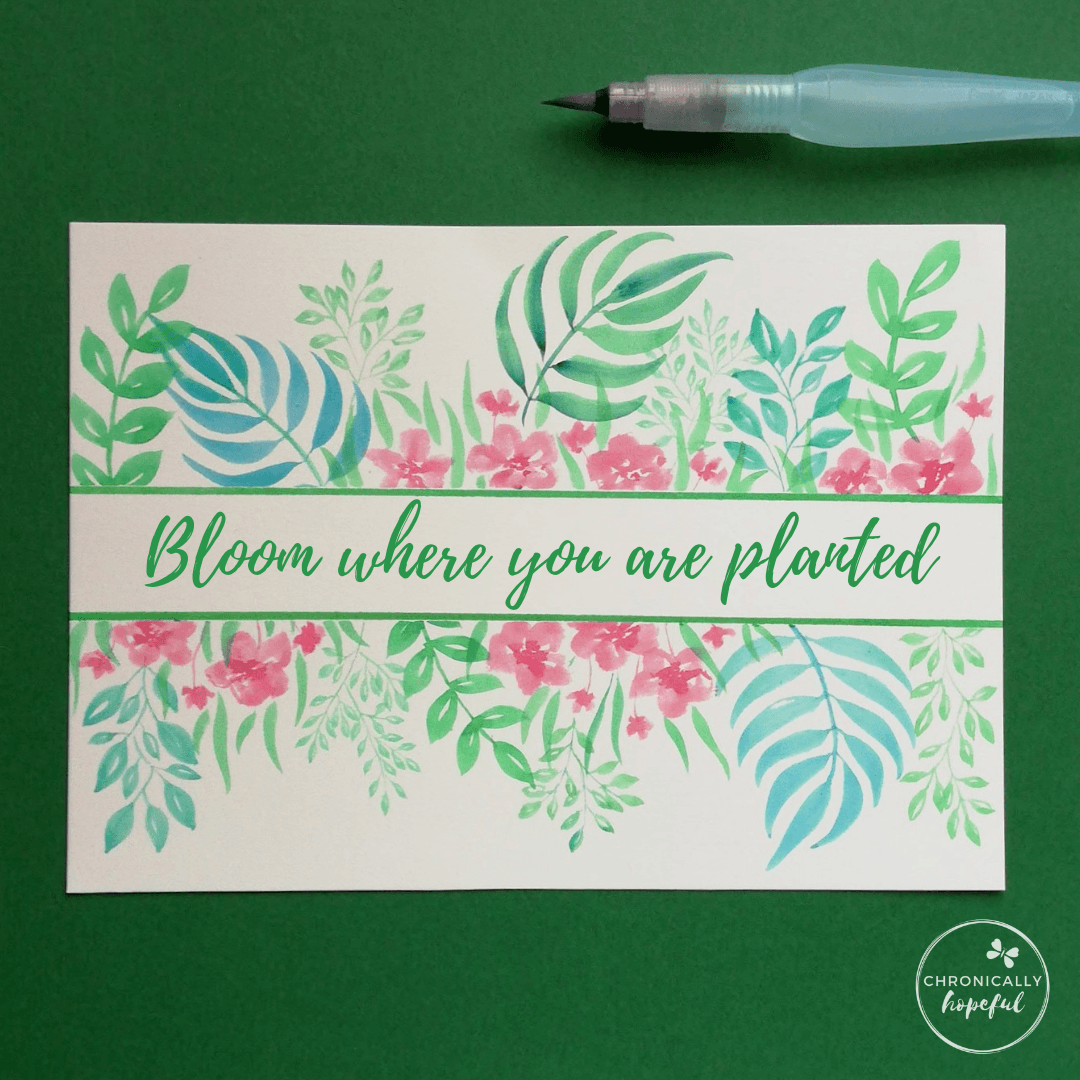 Leaves and flowers painted in watercolour on white card framing the quote bloom where you are planted, by Chronically Hopeful Char