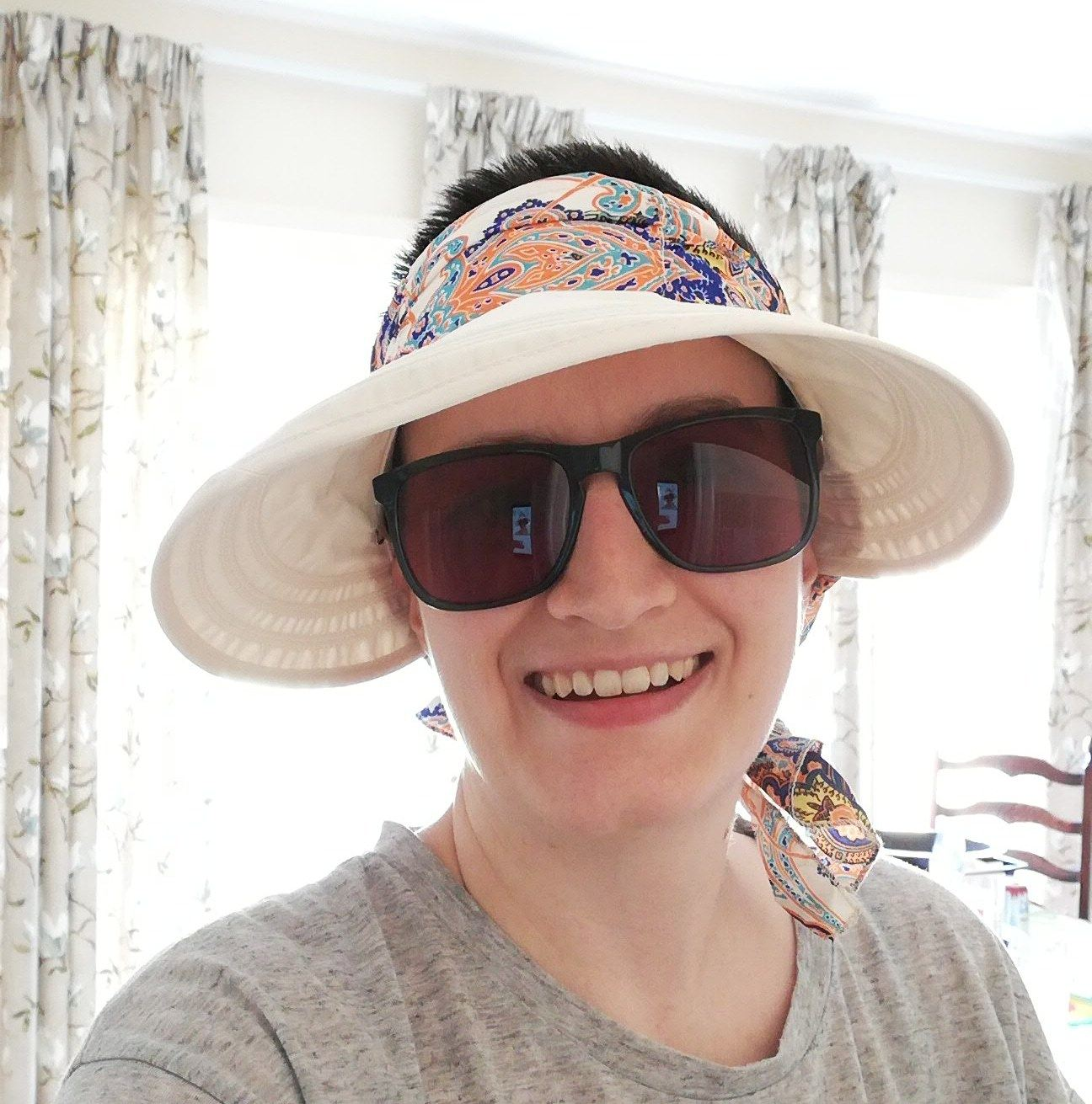 Char wearing a wide-rimmed summer hat and sunglasses. There are large windows behind her with floral curtains hanging.