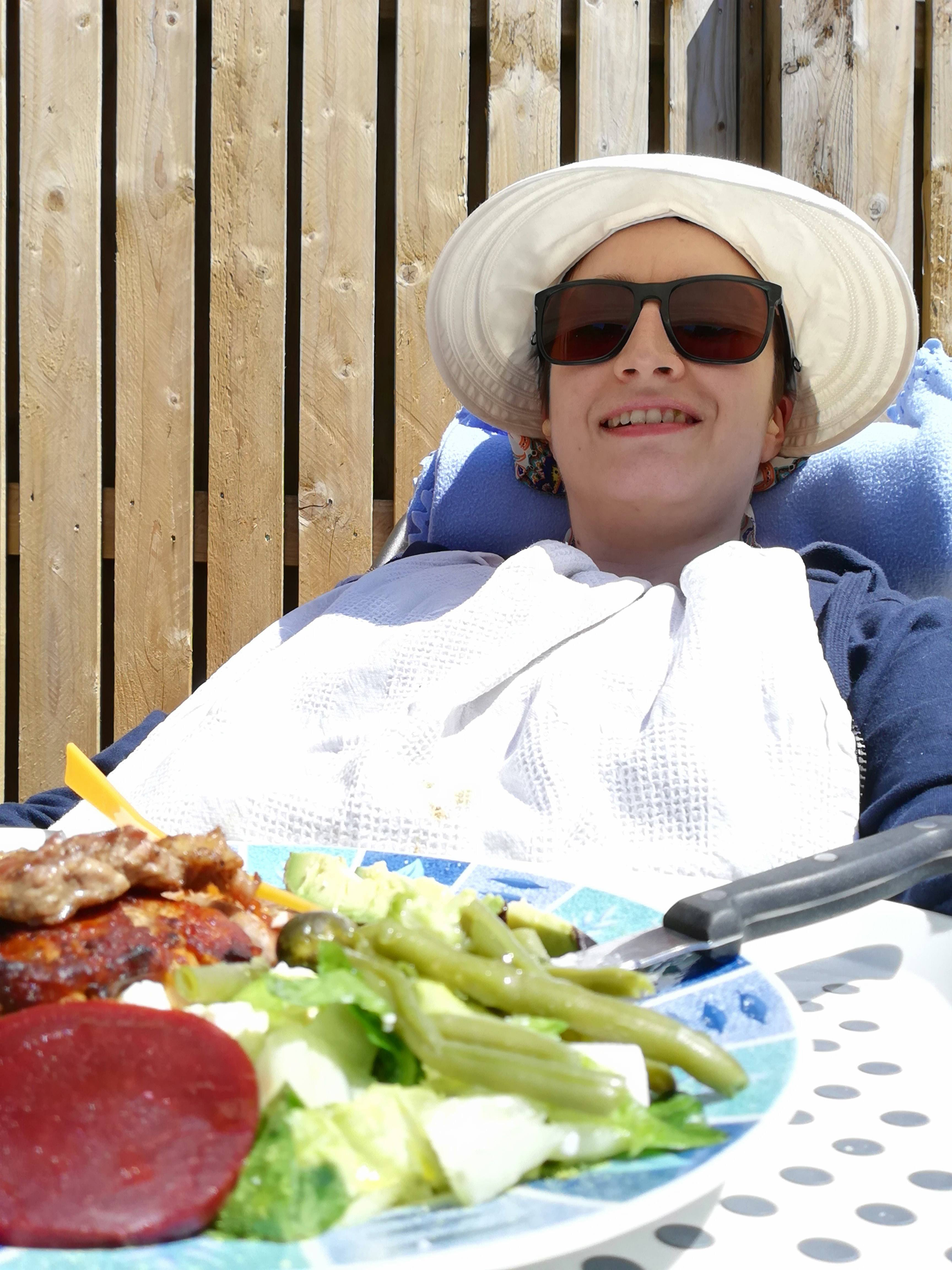 Char lying on garden recliner with a plate of food. She's wearing a sun hat, sunglasses and a bib.