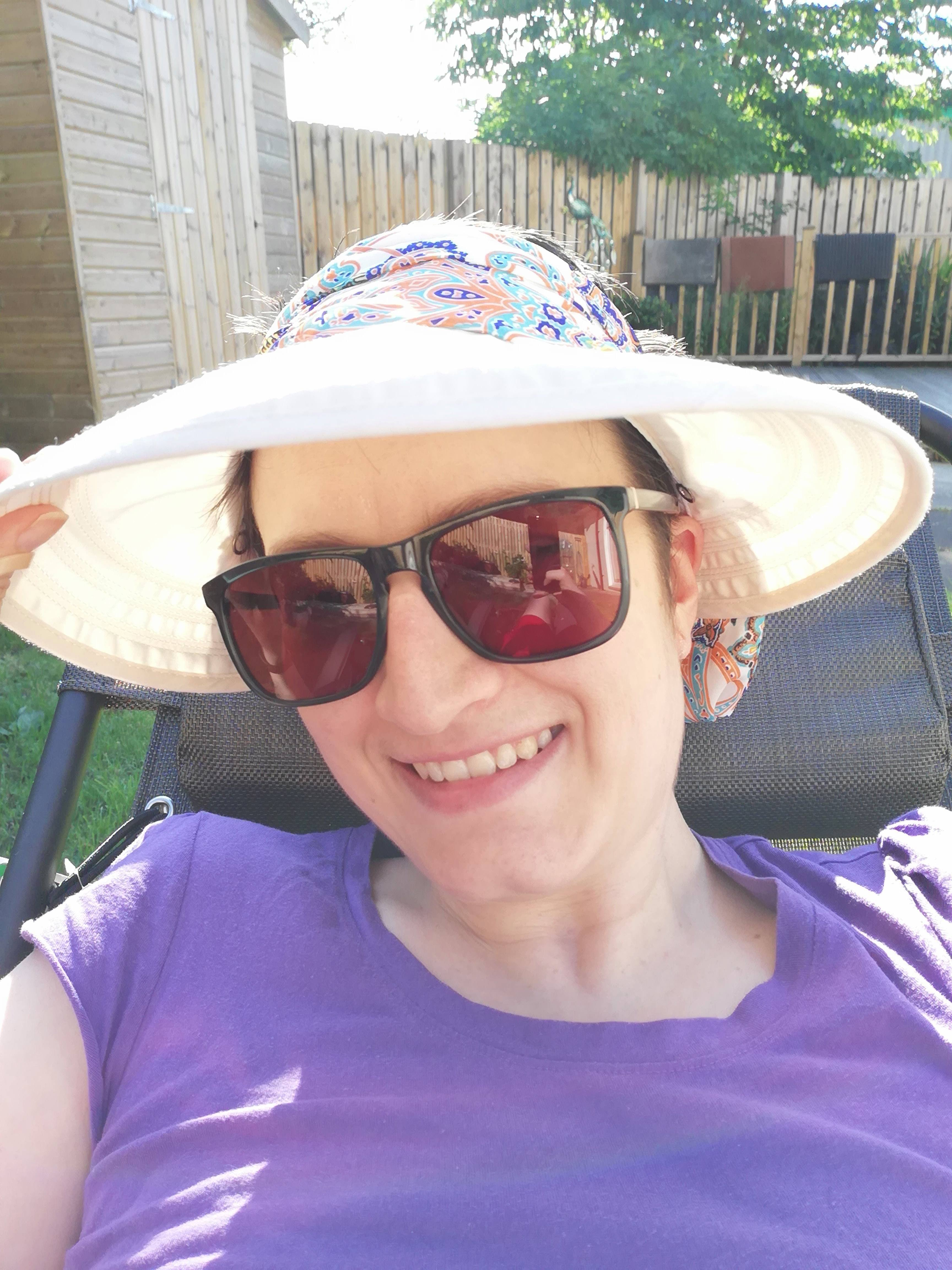 Char lying on garden recliner. She's wearing a sun hat and sunglasses