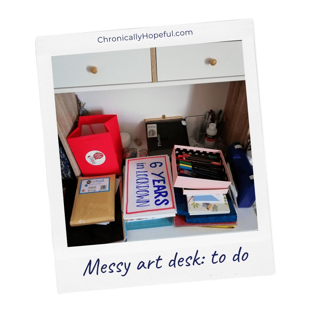 Char's art desk under piles of random items