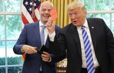 President Donald Trump shows the media a red card during a visit by FIFA boss Gianni Infantino