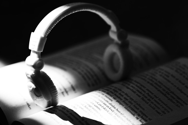 A pair of white over ear headphones balance upright in the spine of an open book. Picture is black and white.