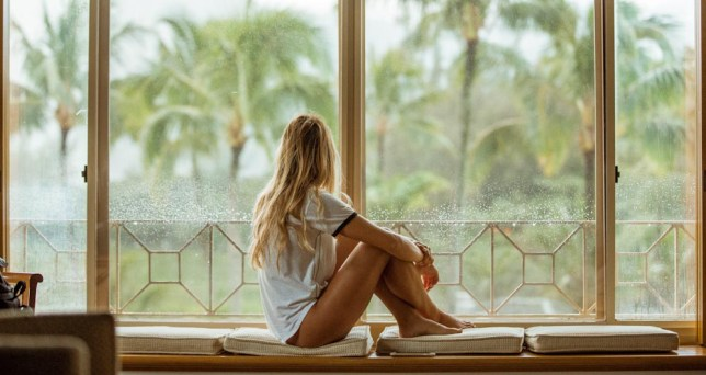 Blonde haired woman sits on window seat looking out the window at palm trees. She has a white tshirt and bare legs.